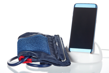 Electronic smart blood pressure monitor or sphygmomanometer with a phone or tablet hooked up to an inflatable arm cuff.  This device is the modern version of the traditional medical instrument for health care. Stock Photo