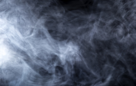 background textures: Smoke from a Vape with light effects on a black background.  The image is an abstract texture with copy or text space.  It has patterns showing movement and depicts a spooky mood with a Halloween theme. Stock Photo