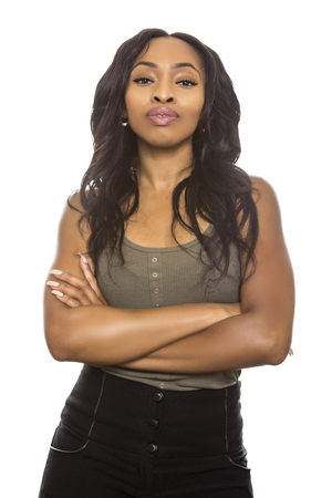 Black female isolated on a white background displaying facial confident expressions.  She is young and of African American ethnicity. Stock Photo - 84911539