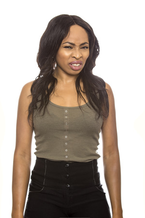 intolerable: Black female isolated on a white background displaying disgust facial expressions.  She is young and of African American ethnicity. Stock Photo