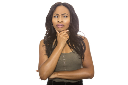 Black female isolated on a white background displaying facial confused expressions. She is young and of African American ethnicity.