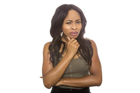 Femmina nera isolata su una priorità bassa bianca che visualizza le espressioni confuse facciali. È giovane e di etnia afroamericana. Archivio Fotografico