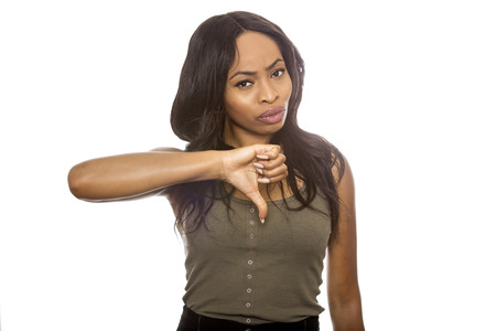 Black female isolated on a white background displaying thumbs down.  She is young and of African American ethnicity. Stock Photo