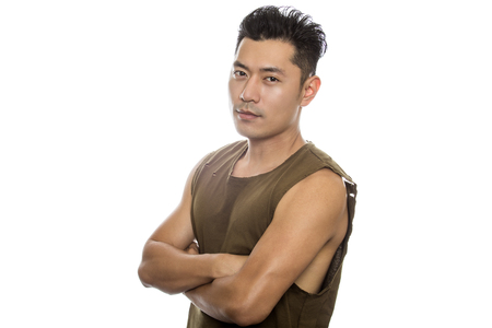 Athletic Asian male with trendy torn sleeveless shirt on a white background.  He is displaying confident expressions or gestures.  The handsome chinese or japanese man is muscular and physically fit