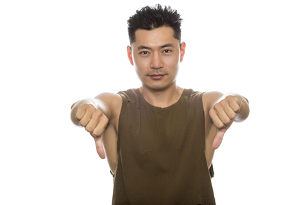 disapprove: Athletic Asian male with trendy torn sleeveless shirt on a white background.  He is displaying disapproval expressions or gestures.  The handsome chinese or japanese man is muscular and physically fit