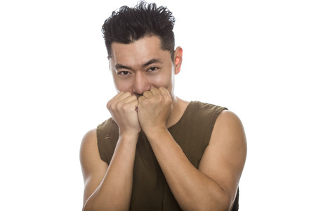 Athletic Asian male with trendy torn sleeveless shirt on a white background.  He is displaying shy expressions or gestures.  The handsome chinese or japanese man is muscular and physically fit Stock Photo