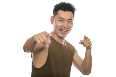 Athletic Asian male with trendy torn sleeveless shirt on a white background.  He is displaying happy expressions or gestures.  The handsome chinese or japanese man is muscular and physically fit