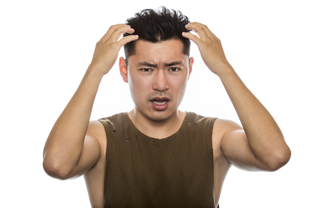 Athletic Asian male with trendy torn sleeveless shirt on a white background.  He is displaying failure expressions or gestures.  The handsome chinese or japanese man is muscular and physically fit