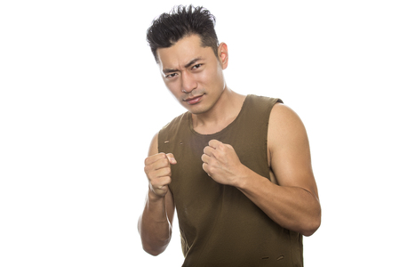 Athletic Asian male with trendy torn sleeveless shirt on a white background.