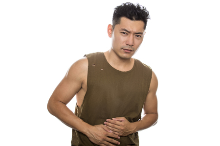 Athletic Asian male with trendy torn sleeveless shirt on a white background.  He is displaying sick expressions or gestures.  The handsome chinese or japanese man is muscular and physically fit Stock Photo