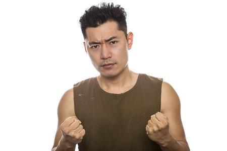 흰색 배경에 트렌디 한 찢어진 민소매 셔츠와 함께 운동 아시아 남성. 그는 분노한 표정이나 몸짓을 표시합니다. 잘 생긴 중국인 또는 일본인은 근육질