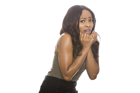 Frightened Black female isolated on a white background displaying facial expressions.  She is young and of African American ethnicity.