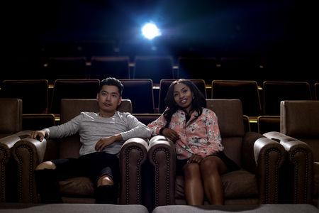 Young interracial dating couple in a movie theater watching a show. The man is Asian and the woman is black.