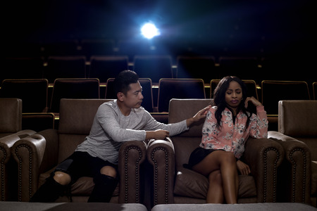 Young interracial dating couple in a movie theater watching a show. The man is Asian and the woman is black. They are fighting and about to break up.
