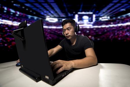 Competitivo videojugador profesional masculino asiático de E Sports que juega un juego de FPS, o MMO en una computadora y que fluye en línea. Foto de archivo