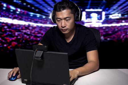 Competitive asian male professional E Sports video gamer playing an FPS, or MMO game on a computer and streaming online.