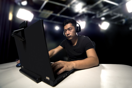 Competitive asian male professional E Sports video gamer playing an FPS, or MMO game on a computer and streaming online in a studio Stock Photo