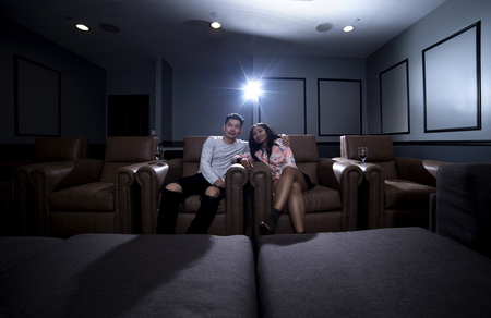 Interracial couple on a movie date in a living room with a home theater system with seats.  They are drinking red wine on glass.  They are watching a movie or television. Stockfoto