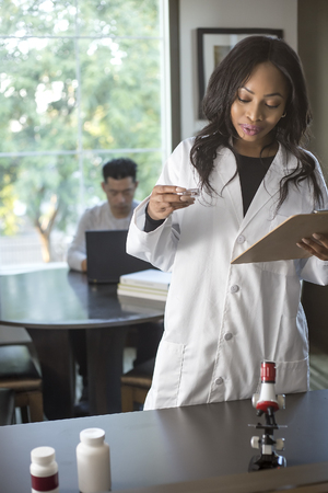 Female scientist in a lab coat researching with her male coed med school student in a campus laboratory.  The woman is learning science and technology in medical industry.