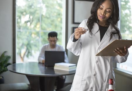 キャンパスの研究室で彼女の男性のコードメッドスクールの学生と研究ラボコートの女性科学者。 女性は医療業界で科学技術を学んでいます。 写真素材 - 91197882