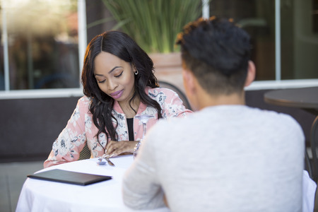 Black female on a blind date with an asian male at an outdoor restaurant.  They are sitting and chatting like speed dating. The image depicts interracial relationships.