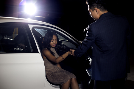 Asian male gentleman assisting his black female date out of a car.  The image depicts interracial dating and manners or a vip celebrity and a valet attendant in a nightclub parking lot.