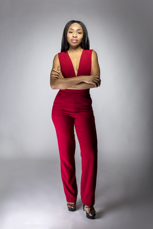 Black African female fashion model wearing red pantsuit for spring design.  The clothing looks semi formal or casual but elegant.  The image depits modern style trend. Stock Photo