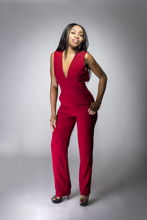 Black African female fashion model wearing red pantsuit for spring design.  The clothing looks semi formal or casual but elegant.  The image depits modern style trend. Zdjęcie Seryjne