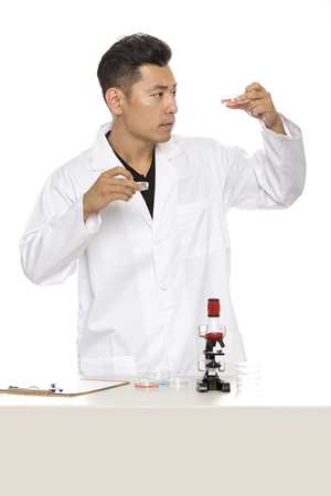 Asian male scientist or microbiologist studying research or experiments with a lab coat and microscope.  He is isolated on a white background.  The image depicts science and medical industry.