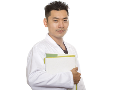 Asian male medical student wearing a lab coat isolated on a white background.  The man is a heathcare worker or an intern.  He is carrying books.