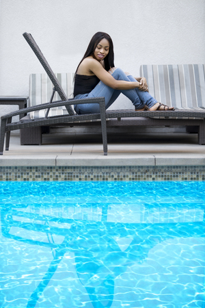 Black female resting by the hotel or resort pool.  The solo tourist is on vacation by herself to have time alone for leisure.  The image depicts tourism or a relaxing spa.  The blue water provides copy space.  Stock Photo