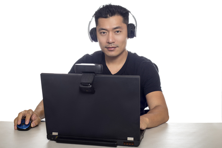 Asian male wearing headphones playing a video game and streaming online with a webcam on a laptop pc.  The image depicts entertainment industry and electronics competition or e-sports.
