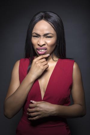 Zwart vrouwelijk model op een donkere achtergrond met walging of geïrriteerde uitdrukkingen.