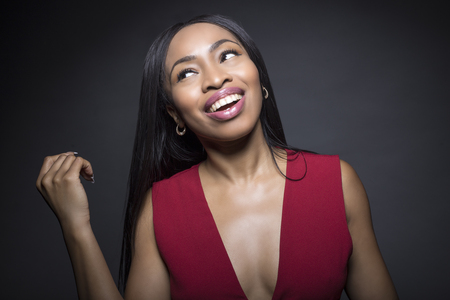 Black female model on a dark background with carefree expressions.