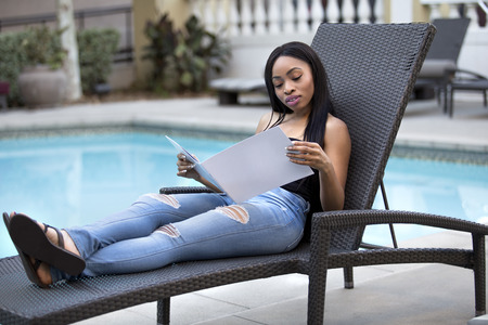 Black female resting by the pool reading a hotel or spa brochure or menu.  She is alone sitting on a lounge on vacation solo. The single lady is looking at a guidebook of available conciere services.