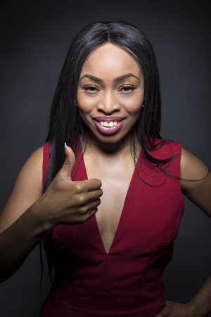 Black female model on a dark background with approval expressions. She is holding her thumbs up.