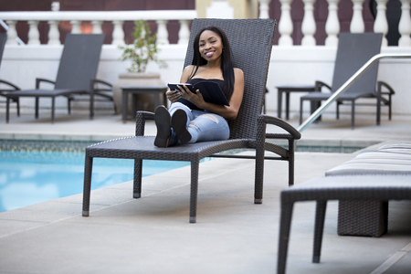 Black female on a vacation in a hotel using a tablet to check on work via the resort wifi.  The woman is relaxing by the pool while using technology to stay connected with business. Stock Photo - 99567536