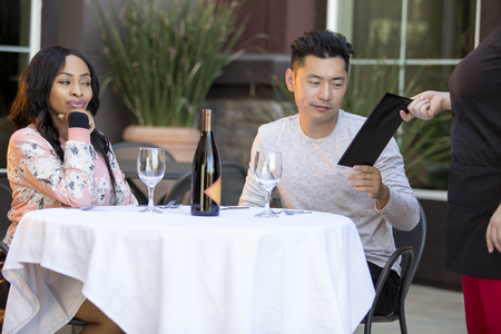 Female hustler on a date with a gullible man paying for her restaurant bill in an outdoor cafe.  The image depicts gentleman or foolish generosity in a dating scenario. Stock Photo