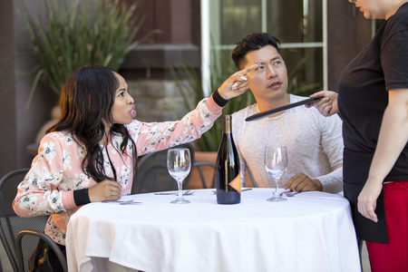 Couple on a date angry at a waitress in an outdoor restaurant.  They are upset and dissatisfied with the customer service or the food in the cafe.  The image depicts the food and service industry.  Stock Photo