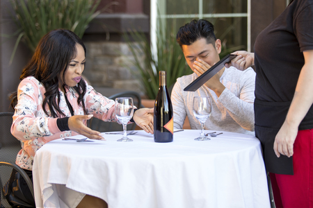 Couple on a date angry at a waitress in an outdoor restaurant.  They are upset and dissatisfied with the customer service or the food in the cafe.  The image depicts the food and service industry.  Reklamní fotografie