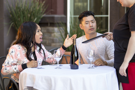 Couple on a date angry at a waitress in an outdoor restaurant.  They are upset and dissatisfied with the customer service or the food in the cafe.  The image depicts the food and service industry.  Stockfoto