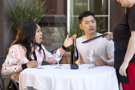 Pareja en una cita enojada con una camarera en un restaurante al aire libre. Están molestos e insatisfechos con el servicio al cliente o la comida en la cafetería. La imagen muestra la industria de alimentos y servicios.