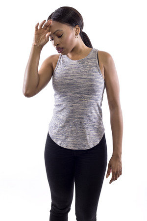 Black female wearing athletic outfit on a white background as a fitness trainer feeling sick