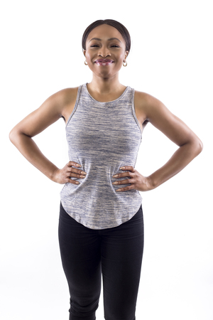Confident black female wearing athletic outfit on a white background as a fitness trainer