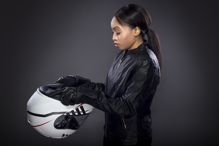 Black female motorcycle rider or race car driver wearing a racing helmet and leather jacket. Part of the gritty woman series, the girl depicts a competitive biker or racer getting ready for competition.
