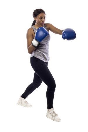Black female isolated on a white background wearing boxing gloves working out with box aerobics cardio.  She is posing with punches and depicts fitness or self-defense and martial arts.