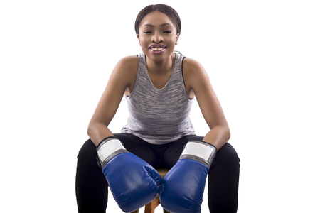 Black female as a gritty woman with boxing gloves for box aerobics or martial arts and self-defense.  She is putting on a game face white sitting down to show determination. On a white background. Imagens - 100375213