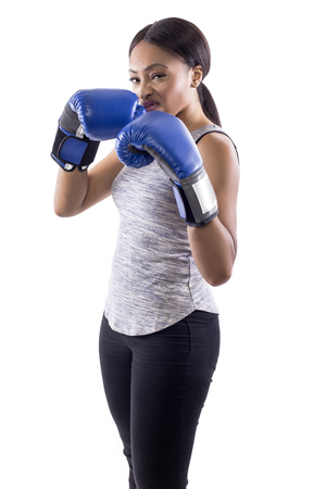 Black female on a white background wearing boxing gloves looking confident and smug.  Part of image set for gritty woman series. Stock Photo