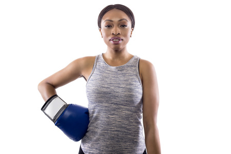 Black female on a white background wearing boxing gloves looking confident.  Part of image set for gritty woman series.