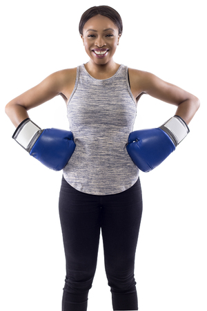 Black female on a white background wearing boxing gloves smiling and looking happy.  Part of image set for gritty woman series.